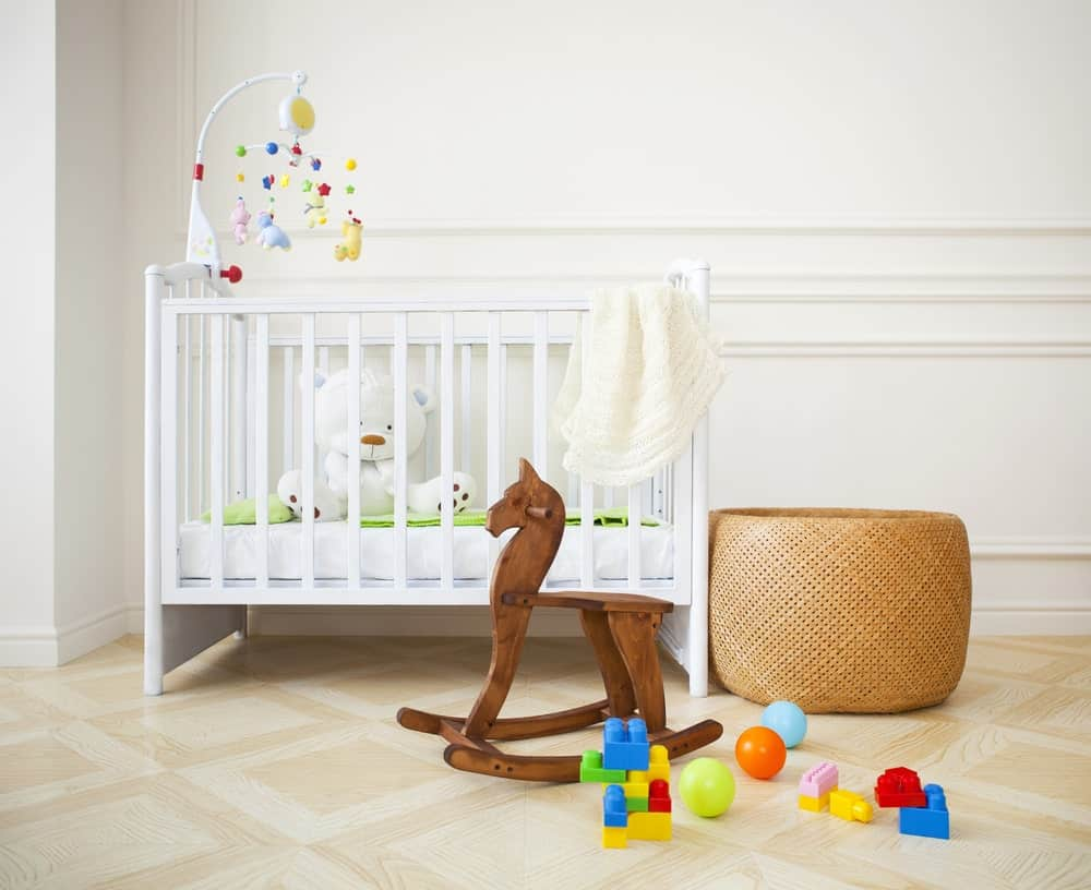 This nursery room features white walls and linoleum flooring.