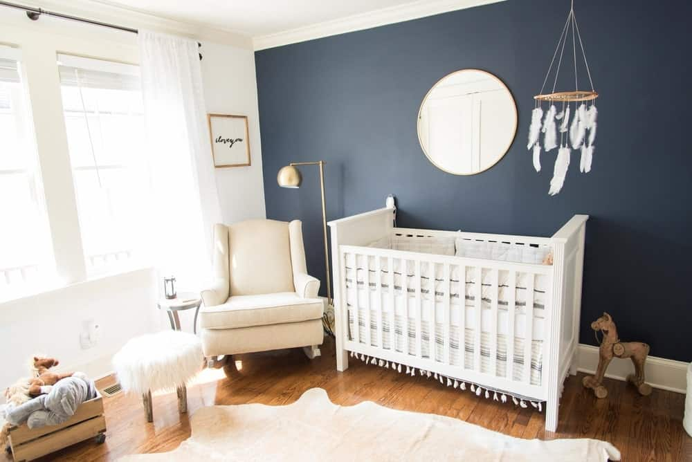 Nursery room with white and black walls along with a hardwood flooring with a rug.