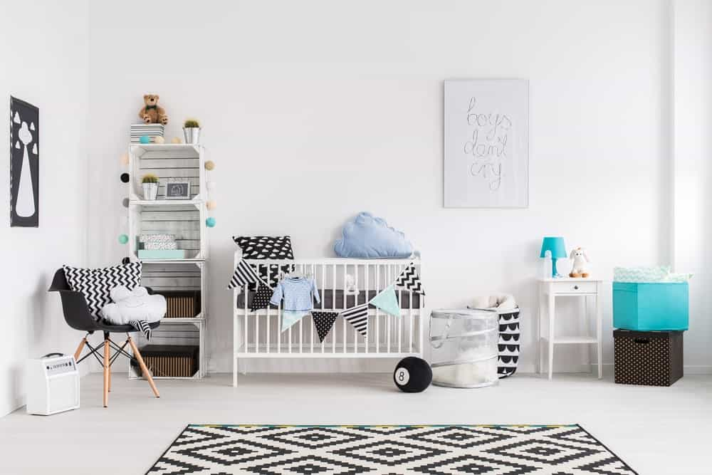 White nursery bedroom with a rug set on the bright finished flooring.