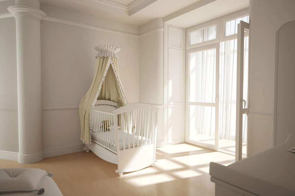 White nursery room with a doorway leading to a personal balcony.