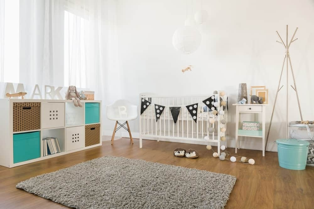 Large nursery room with white walls and curtains along with a white pendant lighting. The hardwood flooring looks cool with the room's style.