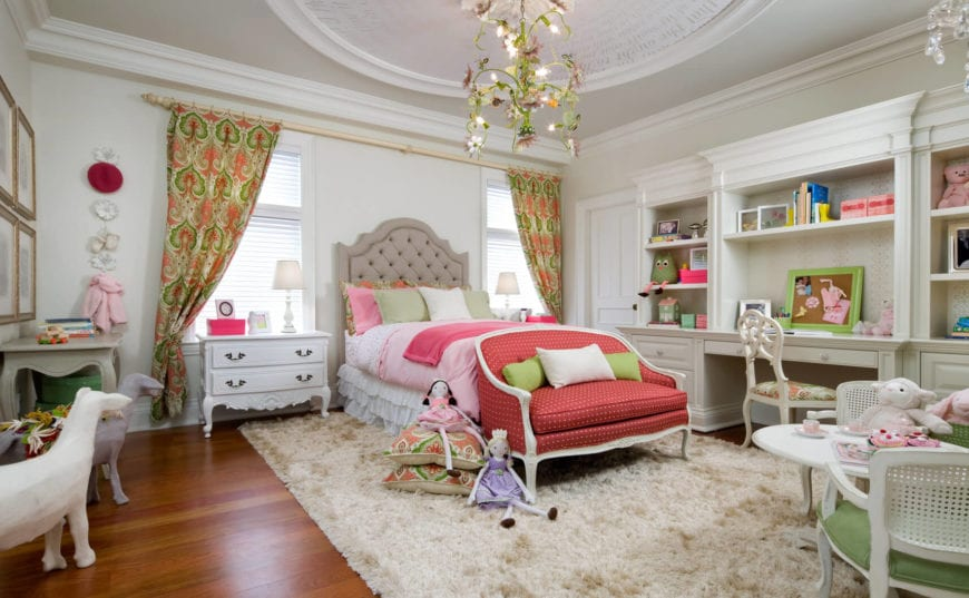 This is a gorgeous girl's bedroom complete with its own tea party area and a study area on the side of the traditional bed with a large cushioned headboard. The study desk is part of a large white wooden structure that also has shelves and drawers.