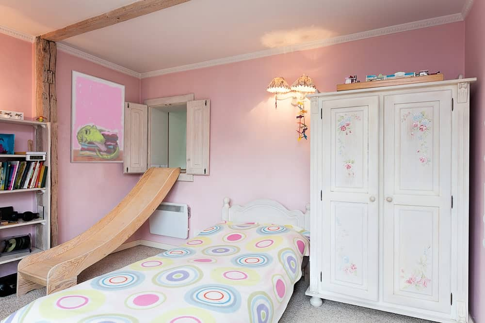 This girl's bedroom features a very interesting entry with a slide coming from the window. The walls look so cute while the lighting looks classy.
