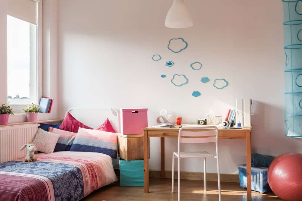 Small girl's bedroom with white walls with blue designs. The bed looks cozy.