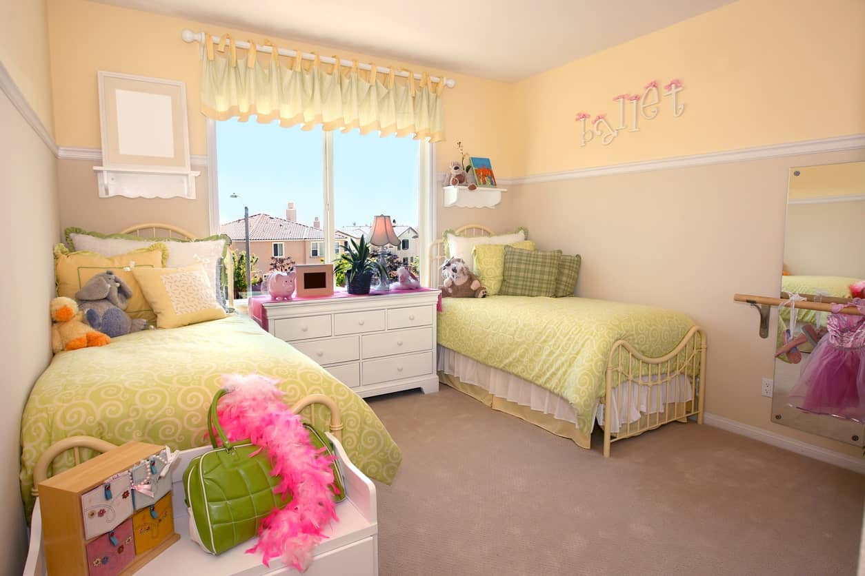 A lovely girls' bedroom with a pair of a bed set on the carpet flooring. The beige walls look perfect together with the room's style.