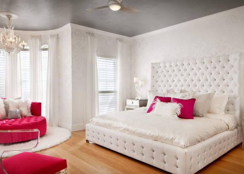 This girl's bedroom offers a classy queen-sized bed with a large headboard matching the elegantly-designed white walls. The seats add color to the room.