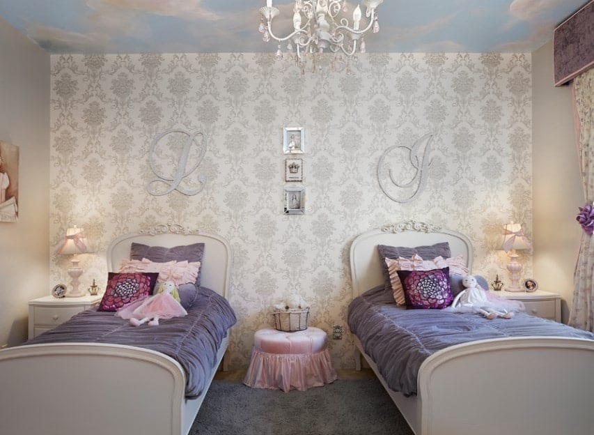 This girls bedroom offers a twin bed with a lovely rug and side tables along with an elegant wall with classy decors.