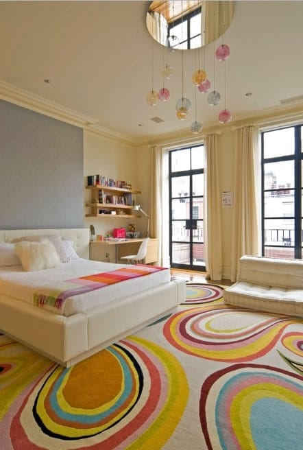 Large girl's bedroom with classy floor rug along with beige walls and window curtains. The bed and the desk are perfectly placed.