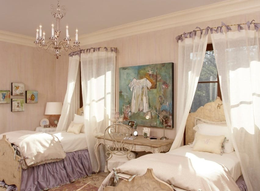 This girls' bedroom offers a twin bed with a lovely desk in the middle, along with artistic wall decors. The chandelier looks absolutely glamorous.
