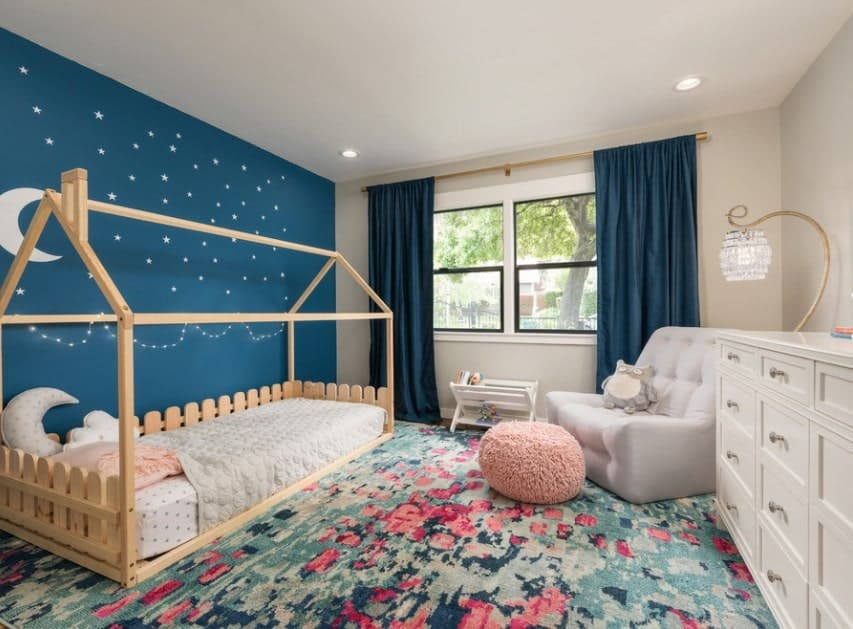 This girl's bedroom boasts a lovely blue wall with very charming stars and moon designs. The blue window curtains match well with the blue wall and rug.