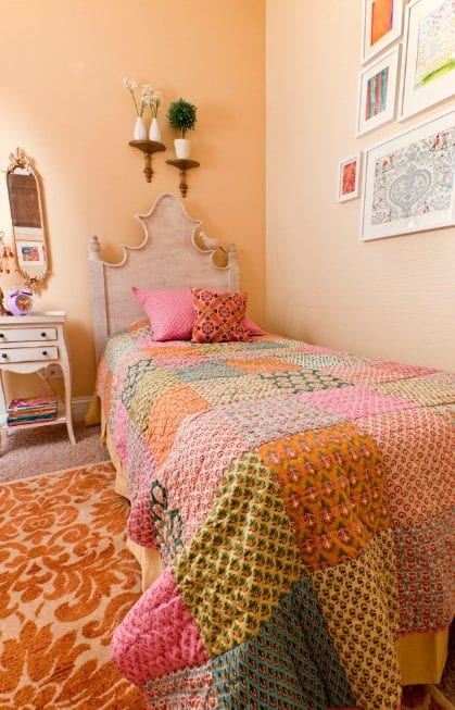 This girl's bedroom boasts carpet flooring topped by a classy rug, surrounded by beige walls.