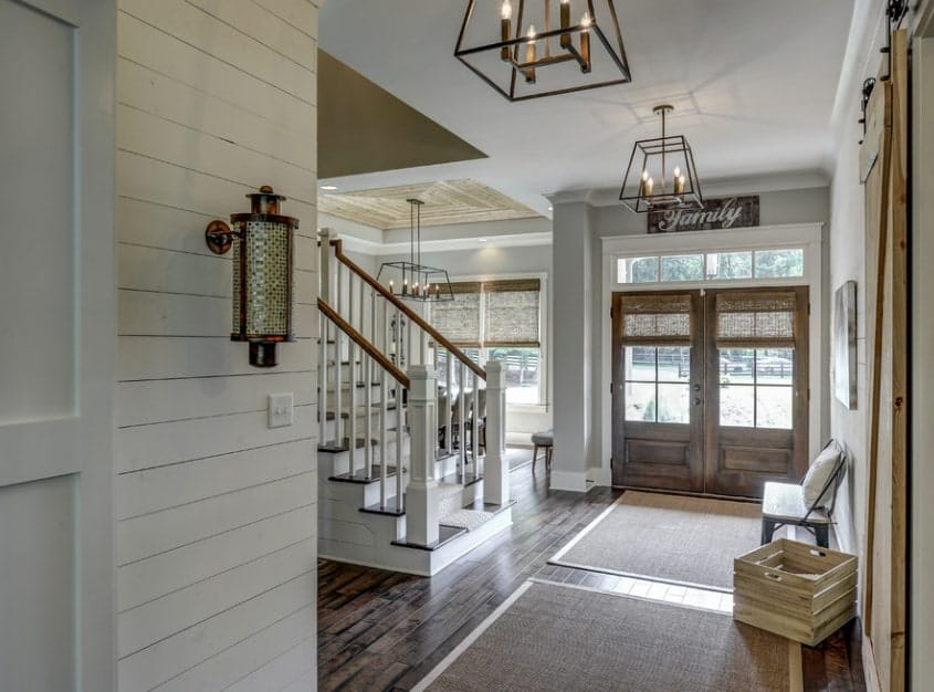 The light gray walls of this charming foyer is a nice complement to the wooden double doors that has glass panels on it. This also complements the hardwood flooring that is topped with woven area rugs underneath wrought iron lantern-like pendant lights from the light gray ceiling.