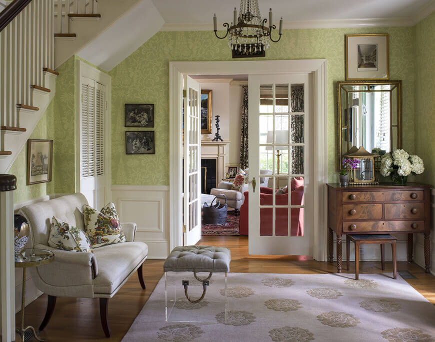 This foyer features its elegant green patterned wallpaper above the white wainscoting. This wainscoting contrasts the hardwood flooring that is mostly covered with a large patterned area rug. This is topped with a small wrought iron and crystal chandelier that hangs from the white ceiling.