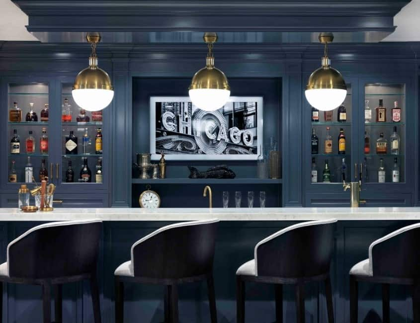 This bar area's counters and cabinetry look very stylish, as well as the decor and lighting.
