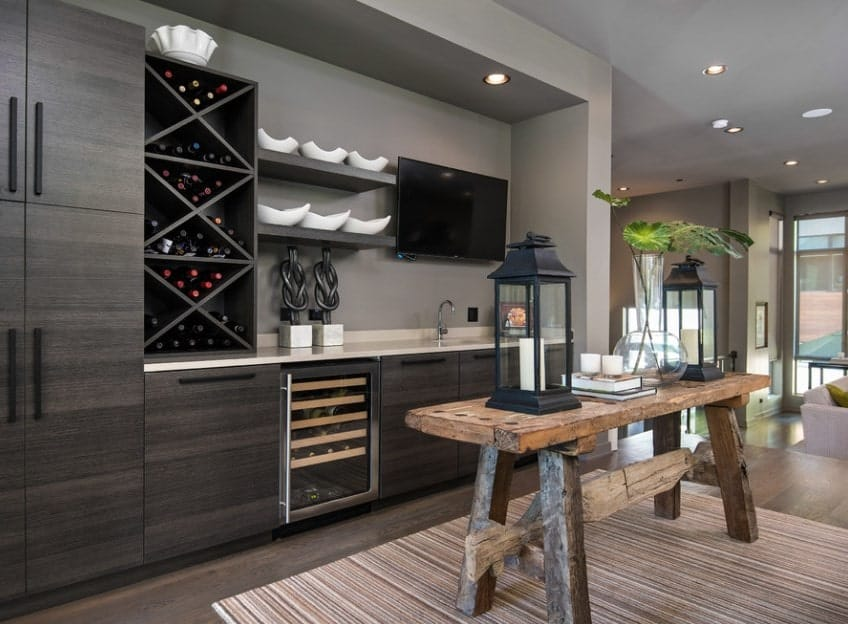 This home boasts a modish bar counter area with a very stylish wine cellar shelving.