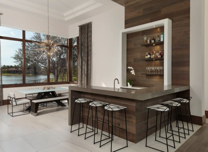 This modern home features a stylish bar set up with a small dining nook on the side near the windows overlooking the beautiful outdoor view.