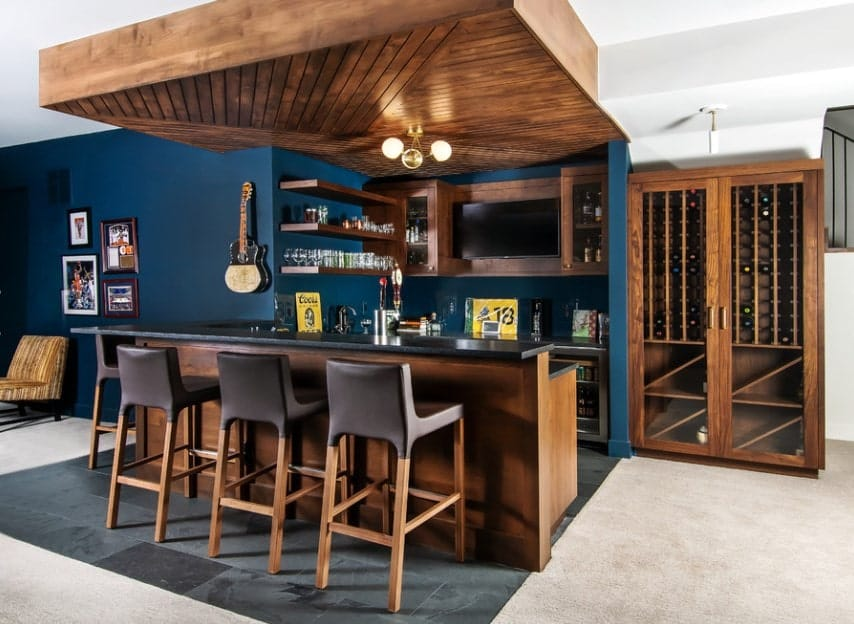 The blue shade on this bar area adds elegance to the space. The bar counter boasts a granite countertop along with a classy set of bar stools.
