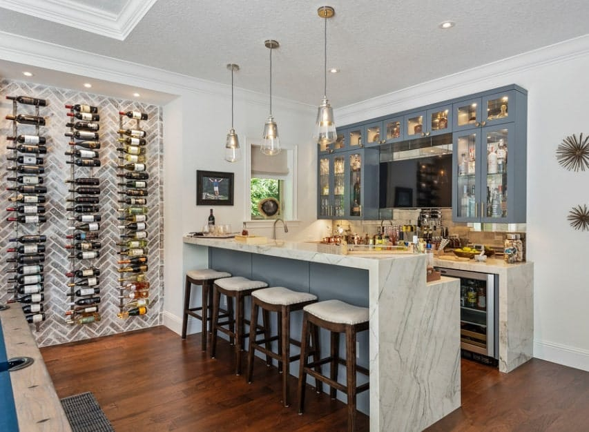 This bar area set on the hardwood flooring features a waterfall-style bar counter with a marble countertop lighted by classy pendant lights. There's an open wine cellar on the side.