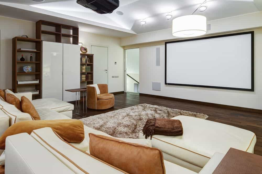A large home theater featuring white walls and ceiling along with a lovely set of sofa seats and a rug on top of the hardwood flooring.