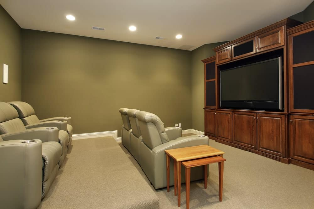 This home theater boasts green walls and white walls. The carpet flooring looks perfect together with the theater seats.