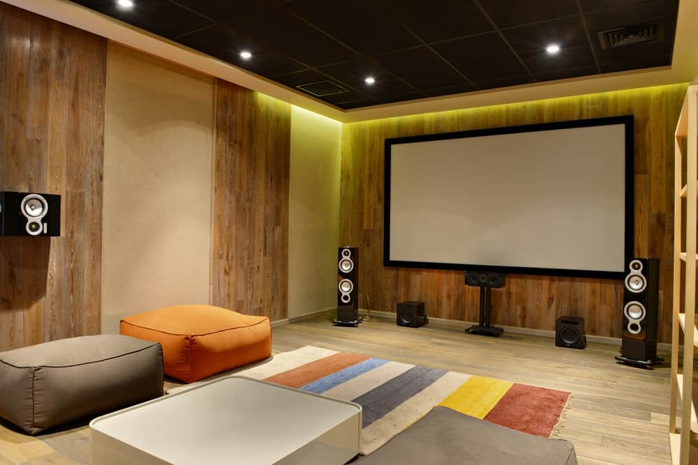 Large home theater with stylish walls and elegant black ceiling. The hardwood flooring matches the walls.