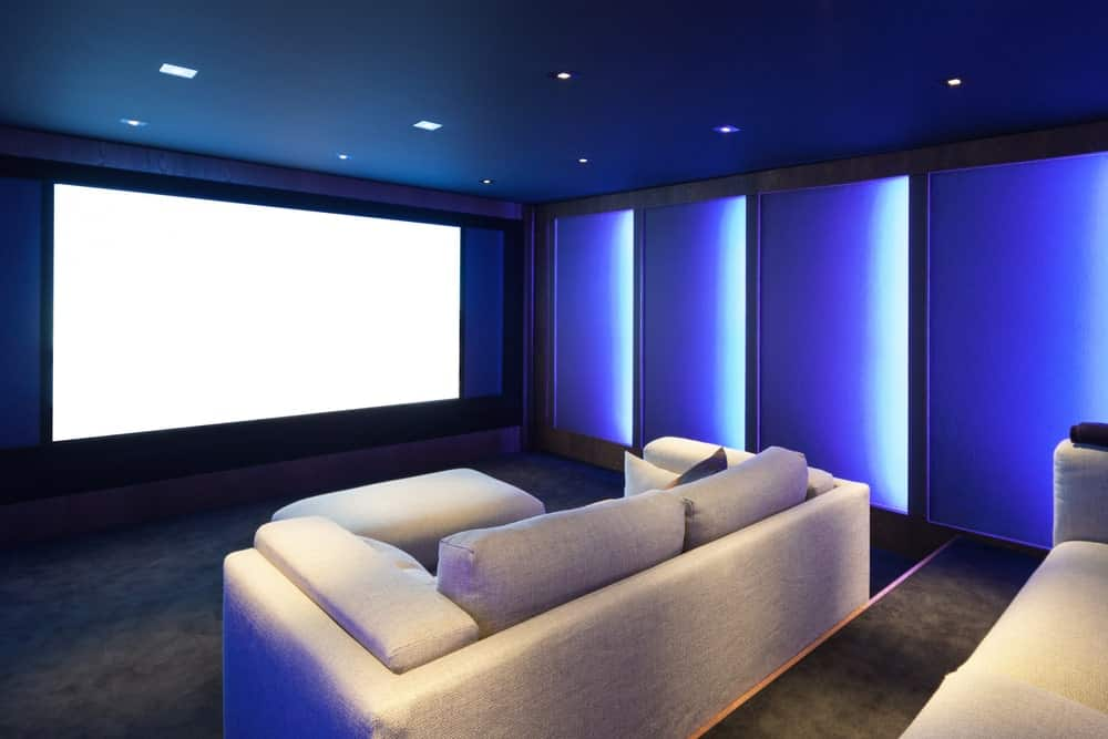 A highly stylish blue-themed home theater with very charming wall lights and ceiling lighting. The carpet flooring looks perfect together with the sofa set.