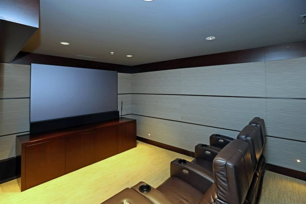 A very modish home theater with gray walls and stylish floors, along with a perfectly placed set of theater seats.