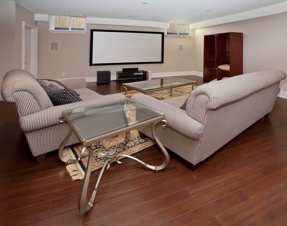 Large home theater featuring cozy sofa set on top of the hardwood flooring.