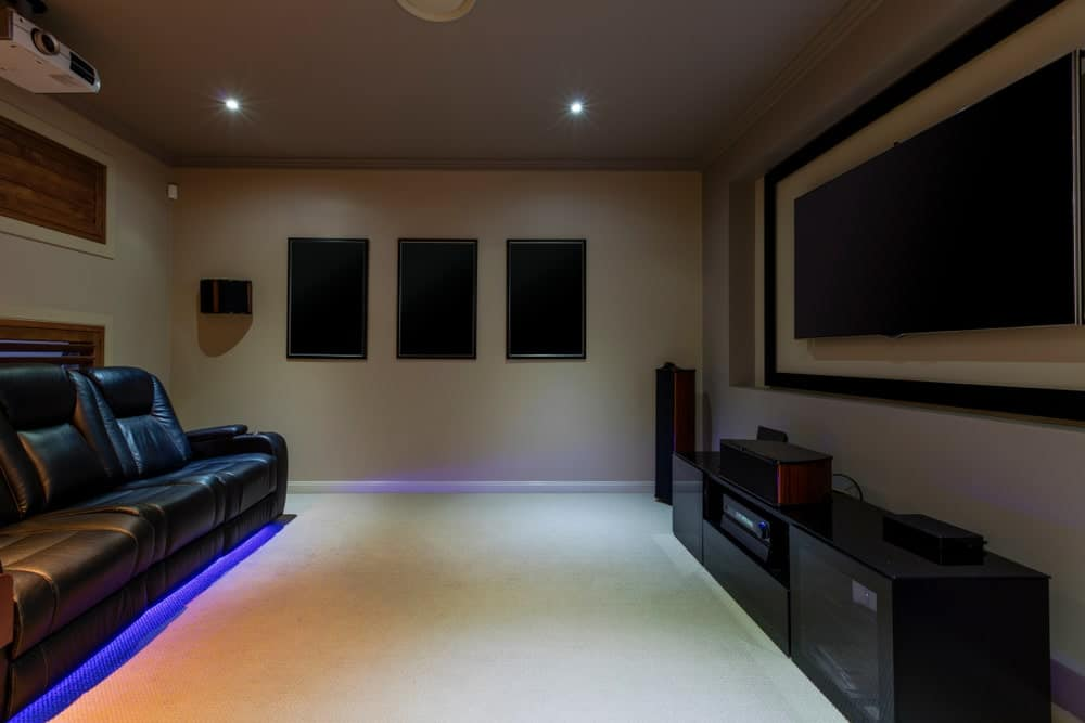 This home theater boasts black elegant theater seats in front of a stylish theater monitor set.