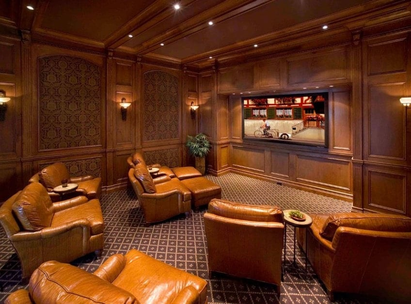 This large home theater features brown walls and ceiling matching the brown leather sectional seats set on the classy carpet flooring.
