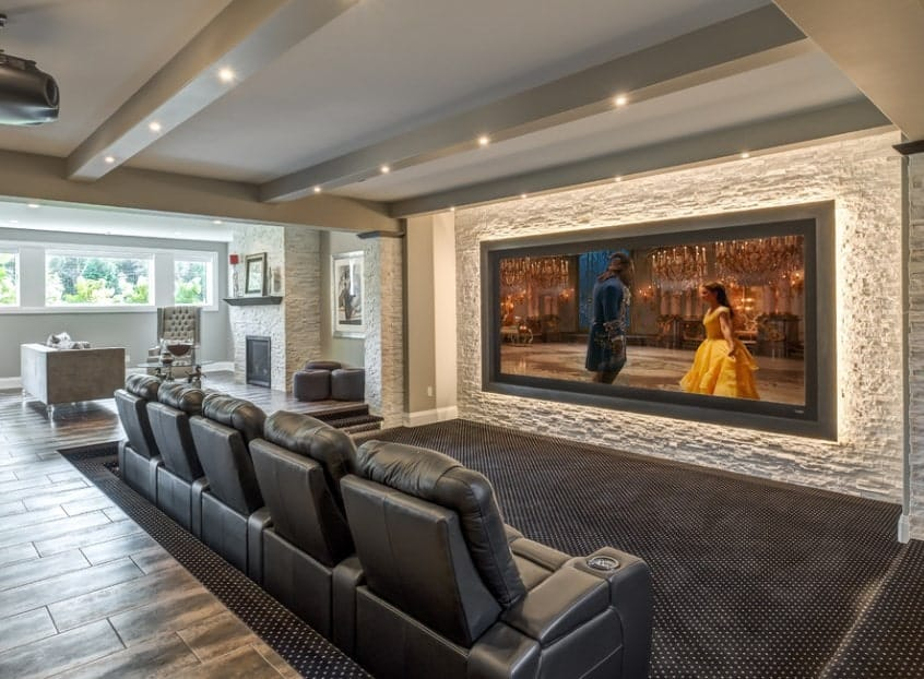 This home features a media room with black leather theater seating set on the stylish carpet flooring.