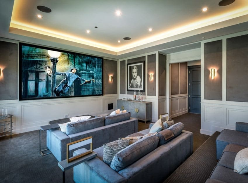 This home features a home theater with classy walls and stunning ceiling along with gray carpet flooring matching the gray sectional seats.