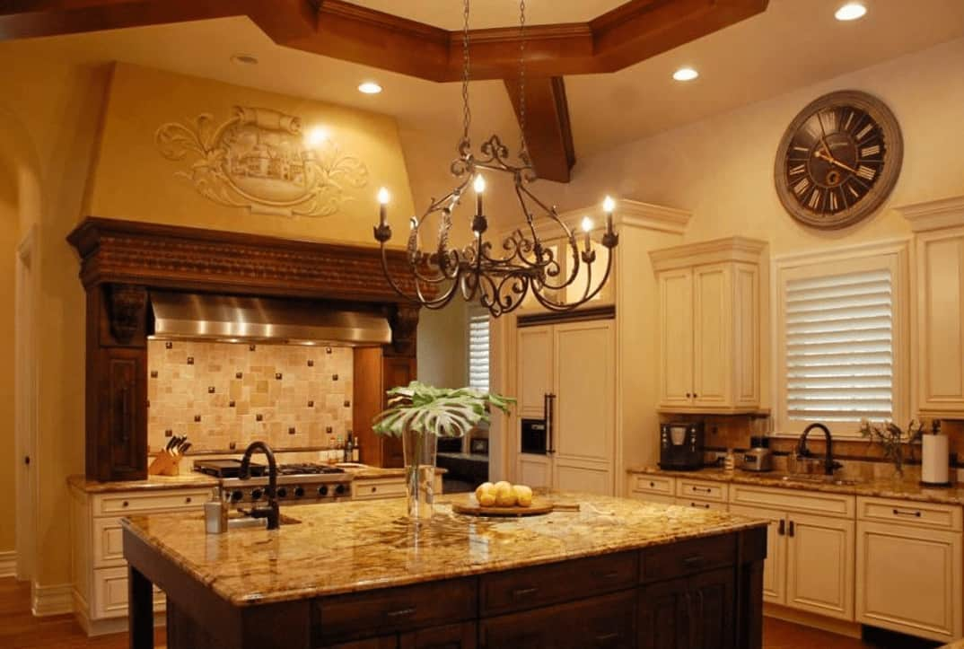 A closer look at the kitchen island shows its gorgeous and wide countertop that is complemented by the dark wooden body below that matches well with the exposed wooden beams and the vent hood above the cooking area beside the island.