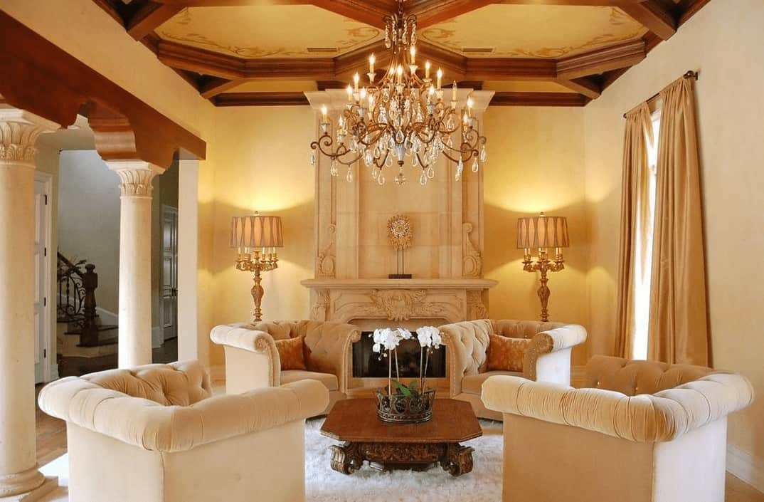The lavish and luxurious living room is topped with a majestic chandelier hanging over the wooden coffee table in the middle of beige cushioned arm chairs that match well with the mantle of the fireplace.