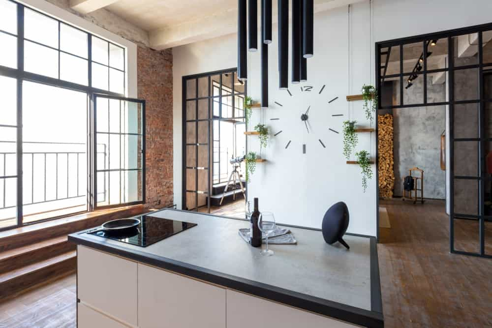Industrial kitchen with a small center island set on the hardwood flooring. The walls and the decors around the kitchen look very stylish.