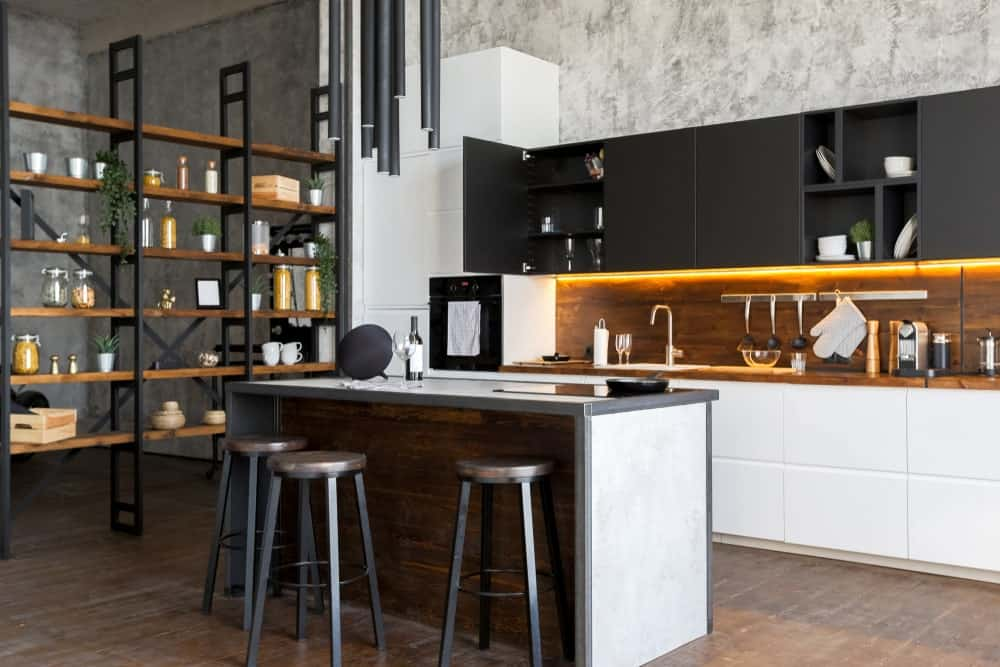 An industrial kitchen with espresso cabinetry, white kitchen counters and center island and hardwood flooring.