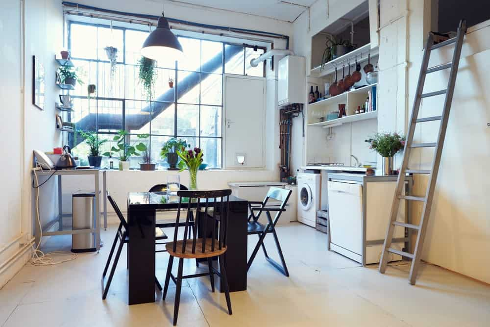 This industrial kitchen boasts white tiles flooring and stylish black dining table set.