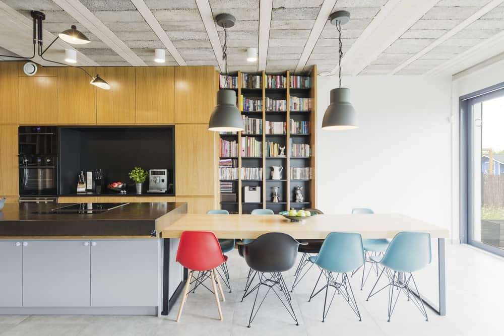 This industrial kitchen offers a dining table set for eight. There are bookshelves as well located in the corner. The center island features a modish countertop.