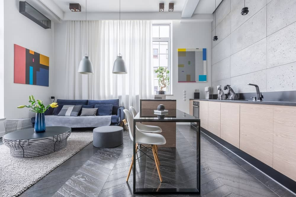 Large industrial kitchen with black countertops on both counters and center island. The herringbone flooring looks stunning together with the white walls with decors.