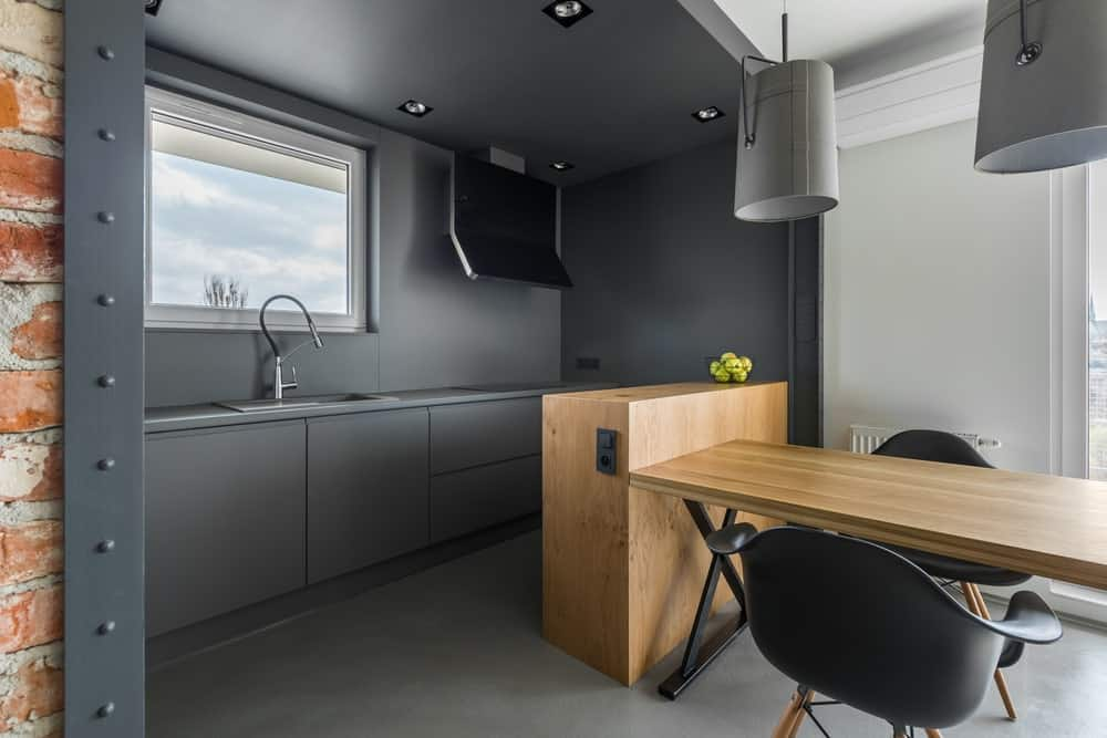 An industrial kitchen with very stylish walls and counters. The dining table set with pendant lights looks absolutely stunning as well.