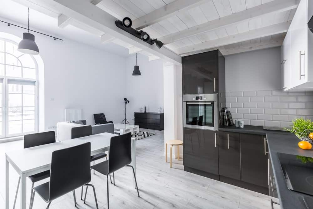 This industrial kitchen is surrounded by white walls and hardwood floors. The dining table matches the kitchen's style.