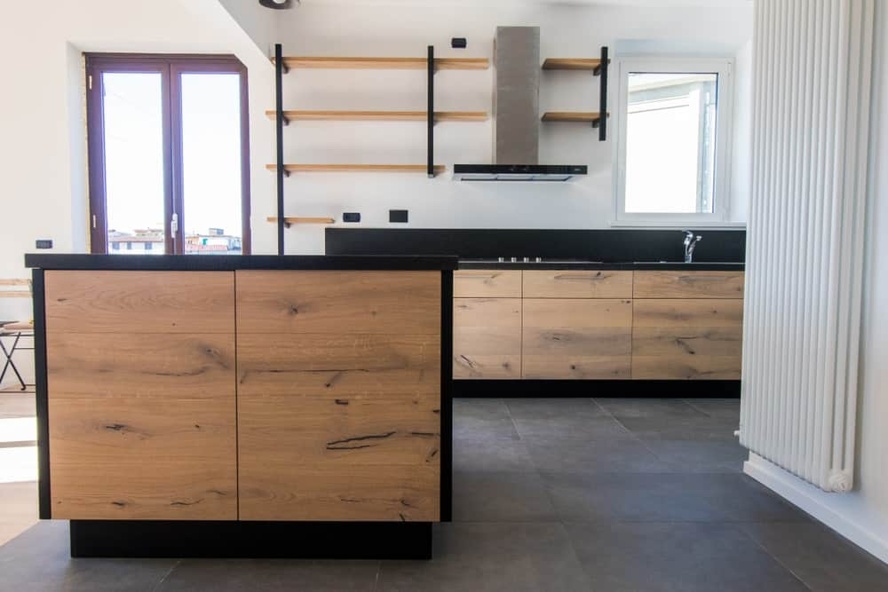 This industrial kitchen basts large concrete tiles flooring and white walls. The counters and the center island both boast black stylish countertops.