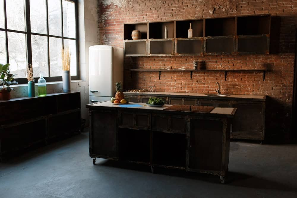 This industrial kitchen features dark finished flooring along with a brick wall with multiple shelves. The counters and the center island look beautiful.
