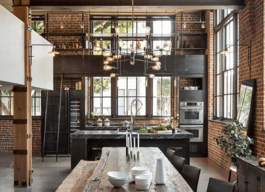 Large industrial kitchen with brick walls and stylish countertops on both kitchen counter and center island lighted by a glamorous ceiling light.