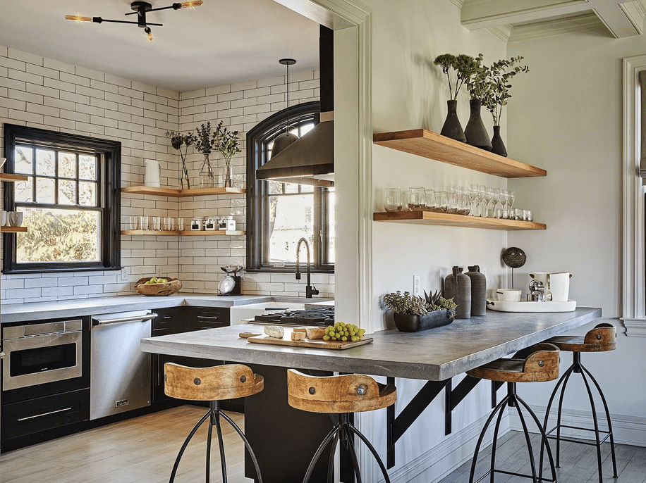 This large industrial kitchen looks absolutely gorgeous. The breakfast bar is so unique while the shelves and the bar stools look lovely together with the hardwood flooring.