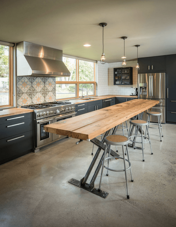 Large industrial kitchen with a breakfast bar made of thick planks lighted by stunning ceiling lights.