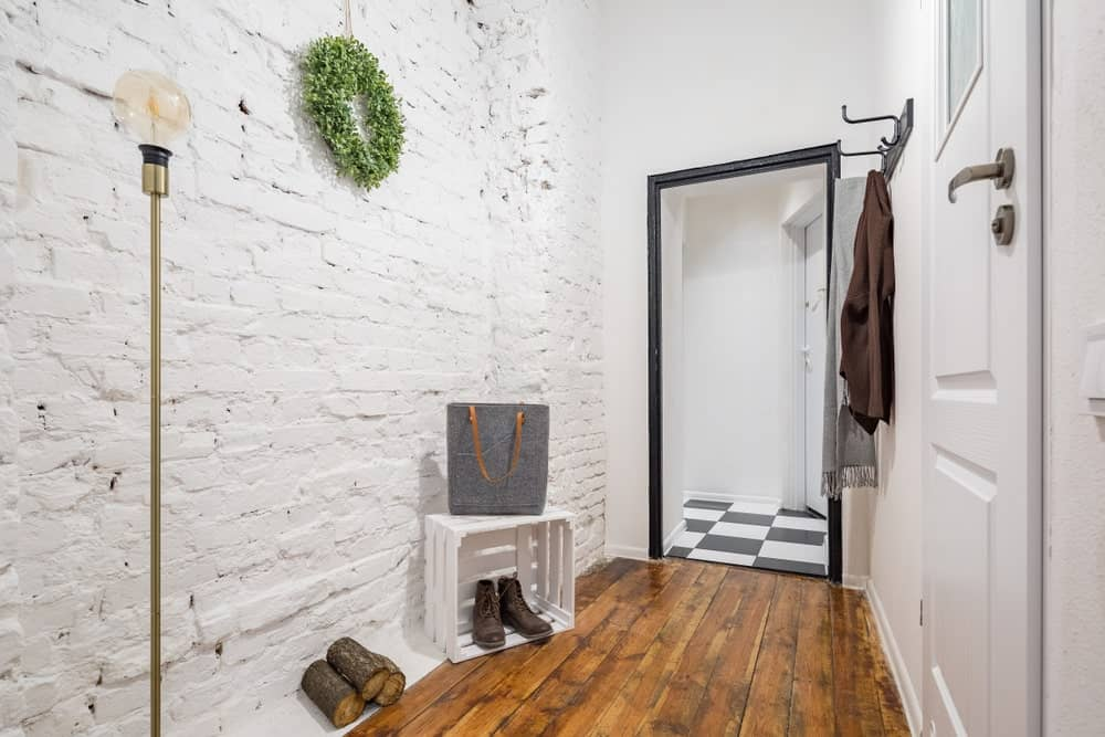 This small Industrial-style foyer has white textured brick wall that is complemented by the distressed hardwood flooring that transitions to a black and white checkered flooring upon crossing the threshold of the entryway to the rest of the home.
