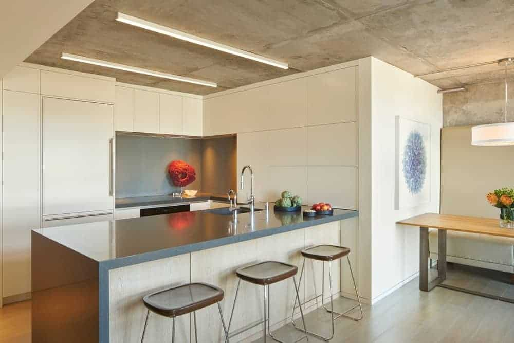 The ceiling is made of gray concrete that matches with the waterfall kitchen island. The ceiling has a couple of beige lights that match the kitchen cabinets of the L-shaped peninsula that houses the various appliances.