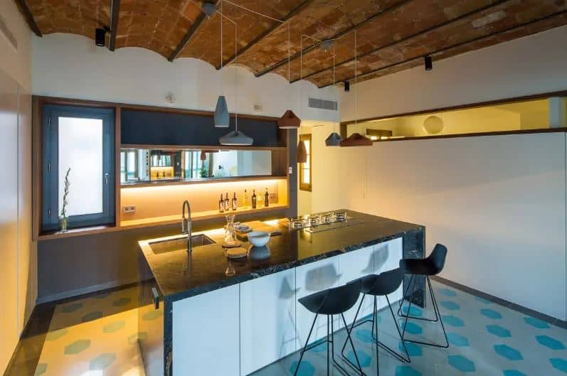 This industrial-style kitchen has a unique ceiling made of brick with a small arches to it. This is matched with an equally unique flooring that has gray and green hexagonal tiles arranged in a polka dot pattern. This is a nice background for the simple waterfall kitchen island and small peninsula.