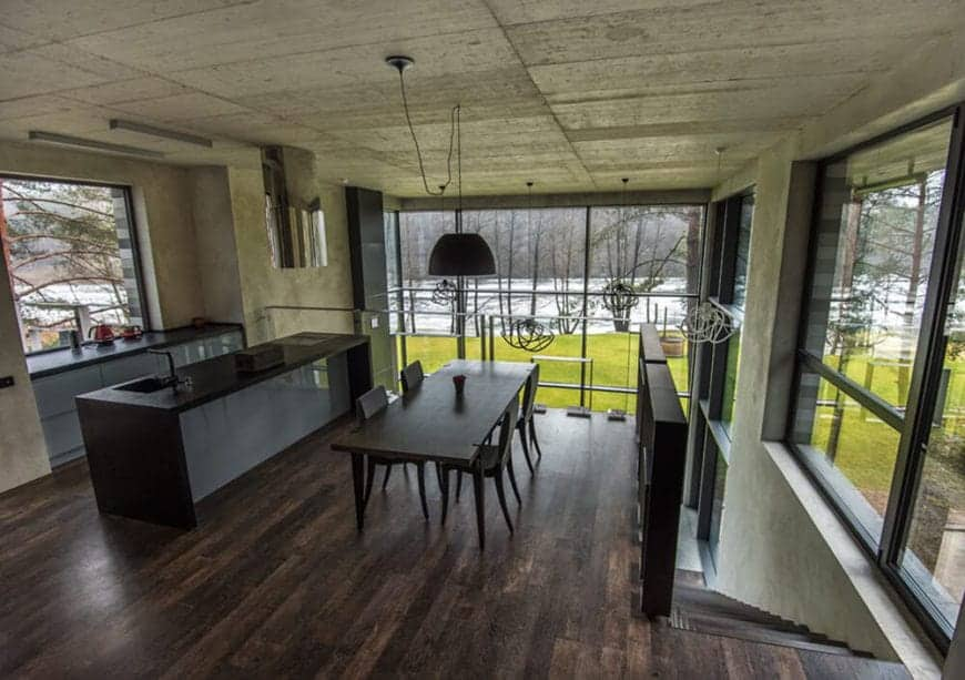 This is a second floor kitchen with a hardwood flooring that blends with the kitchen island and an industrial-style gray concrete ceiling and walls brightened by the large glass windows that feature a wonderful landscape scenery outside.